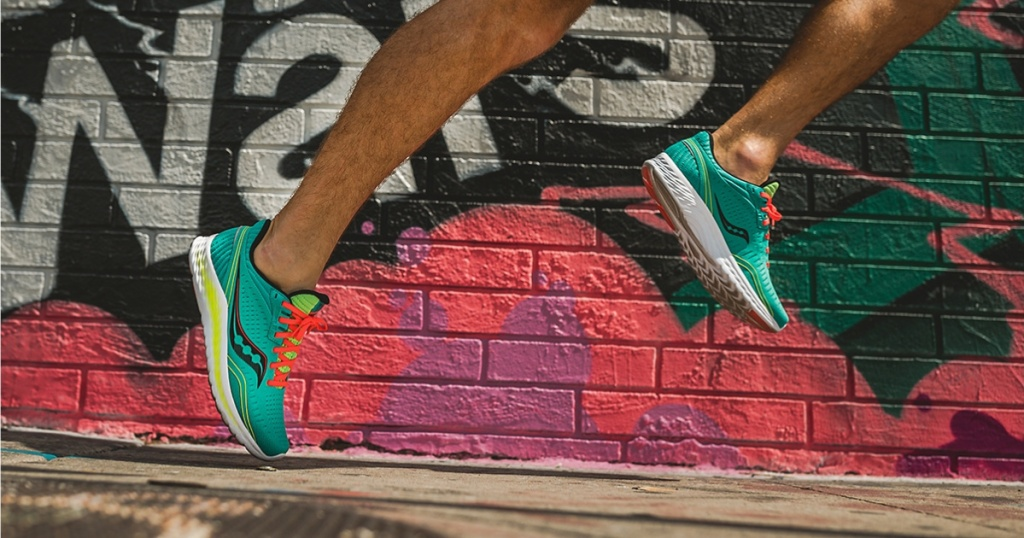 man running in green and orange sneakers in front of graffiti wall