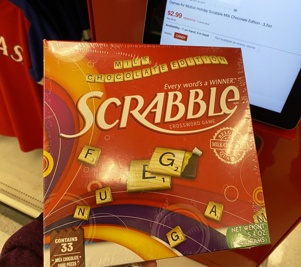 person holding up scrabble holiday edition game at target price scanner
