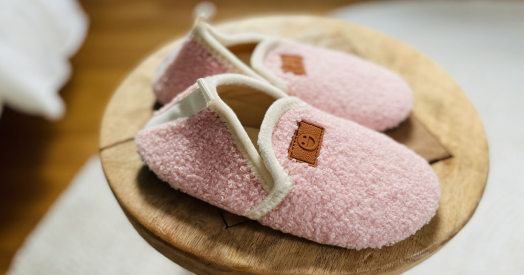 pair of kids pink sherpa slipper on round wood table