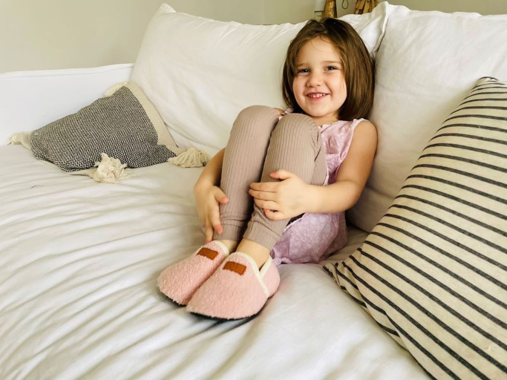 girl sitting on a couch wearing slippers