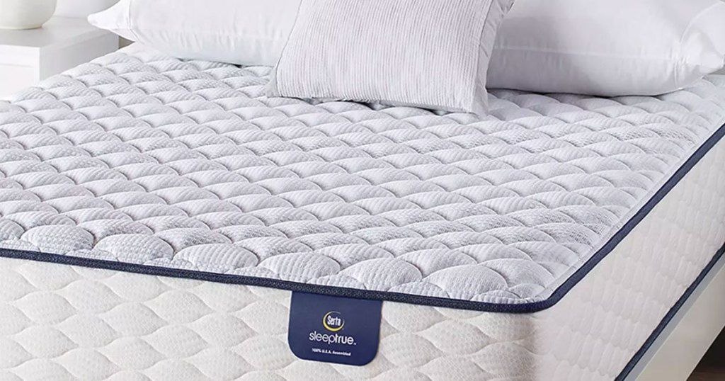 white and light blue serta mattress with pillows on top