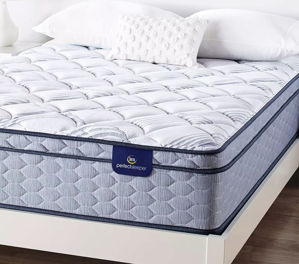white and blue serta mattress on a white bed frame with pillows on top of the mattress