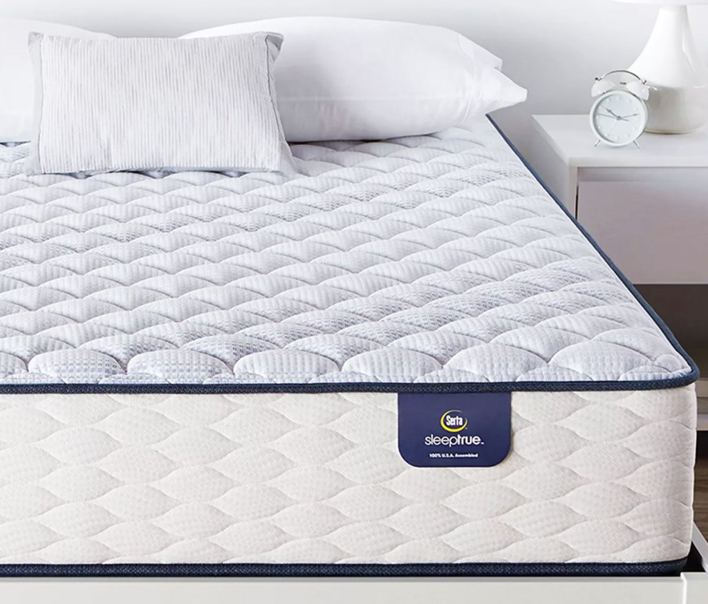 white and light blue serta mattress on a white bed frame with pillows on top of the mattress