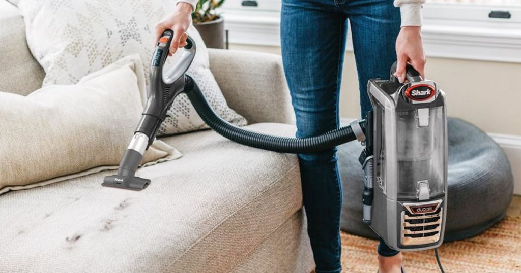 woman using shark lift-away vacuum to clean pet hair on a couch