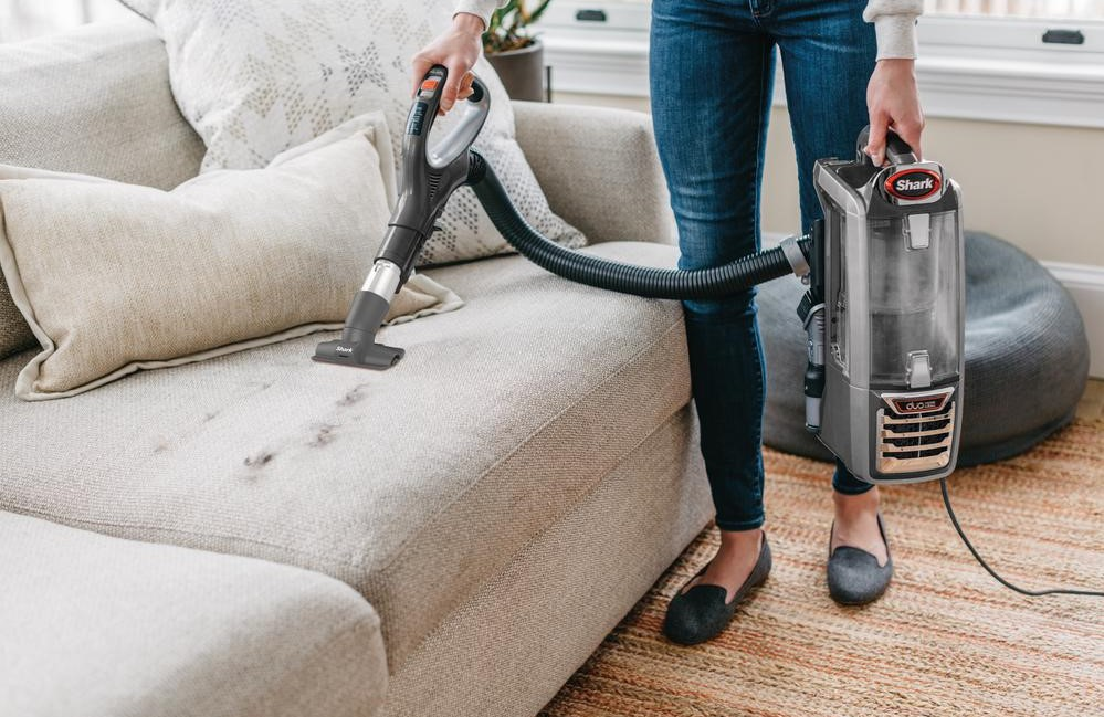 woman vacuuming a couch