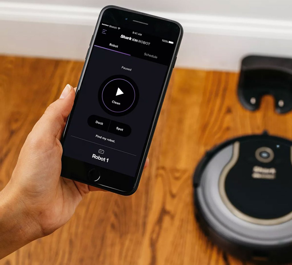person holding smartphone showing shark app with shark robotic vacuum in background