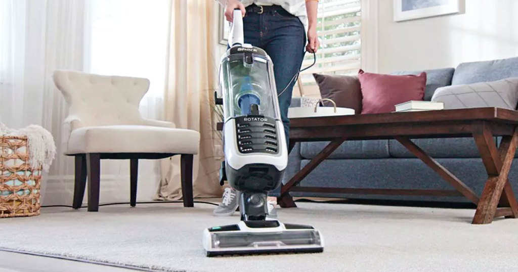woman pushing a grey and white shark upright vacuum on area rug