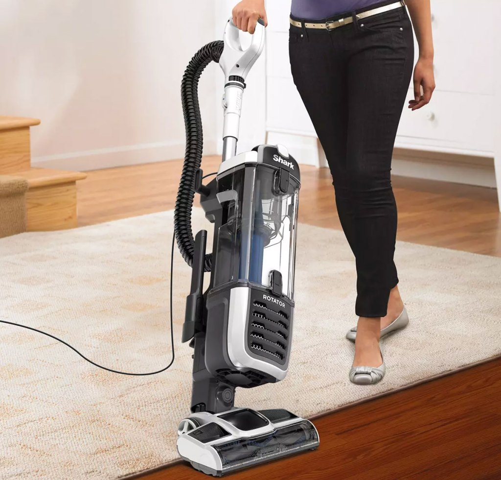 woman in black pants pushing a grey and white shark upright vacuum on area rug