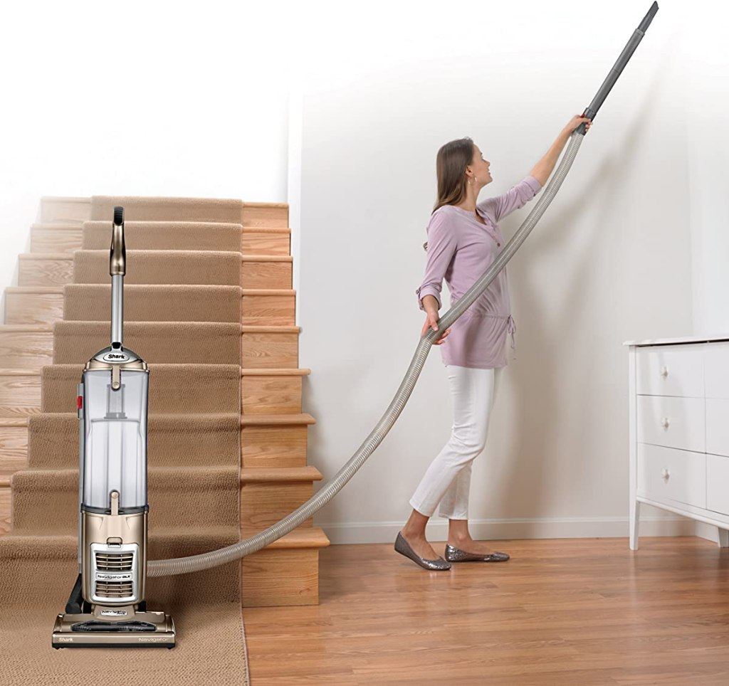 woman vacuuming the ceiling