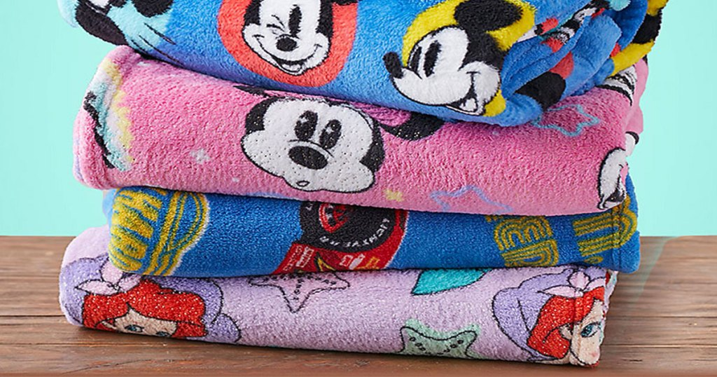 stack of folded disney themed throw blankets