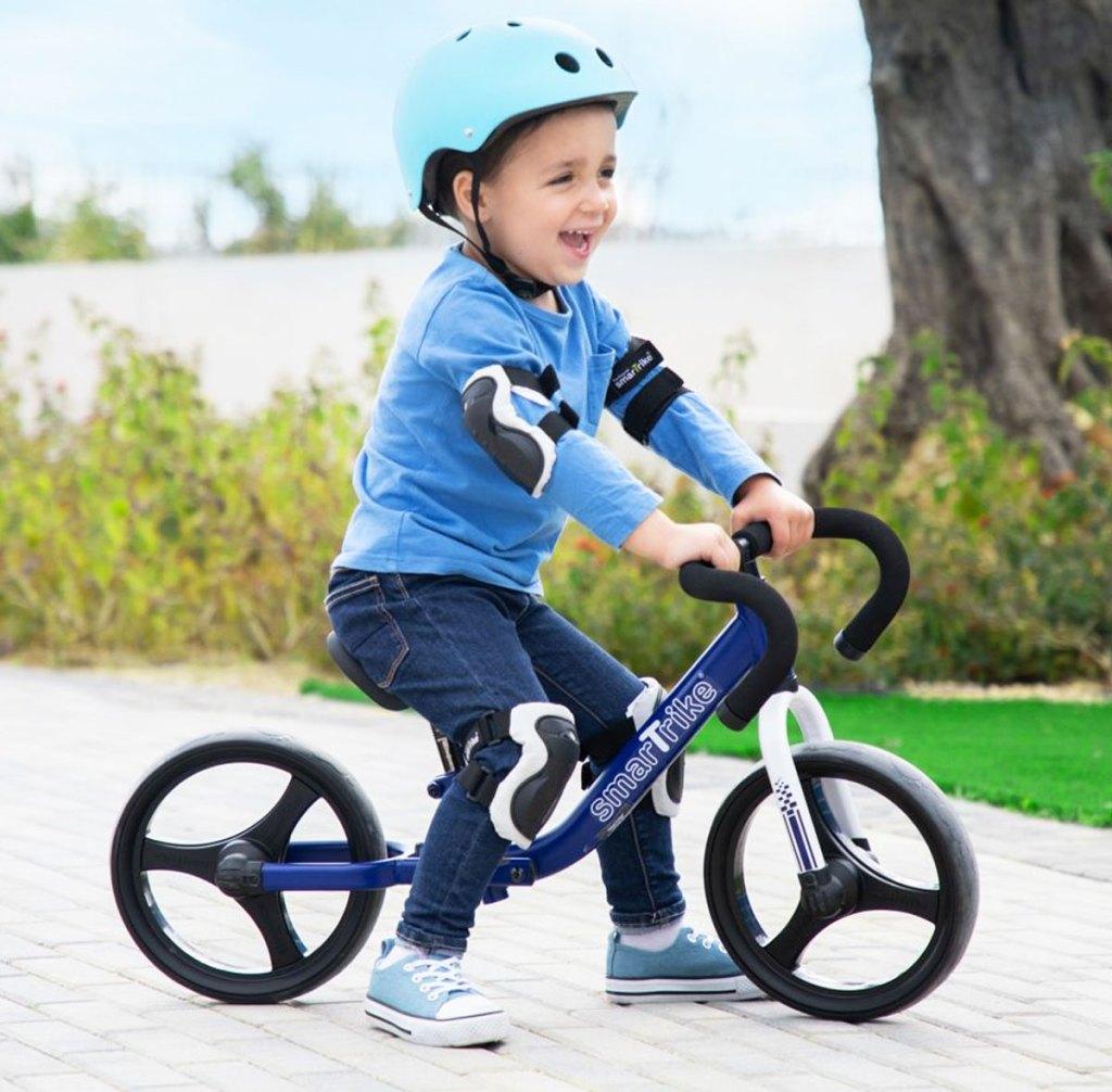 boy on a blue balance bike