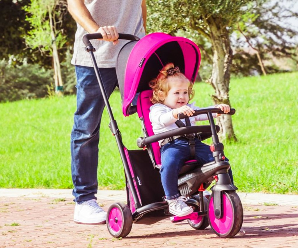 parent pushing toddler in pink and black tricycle stroller