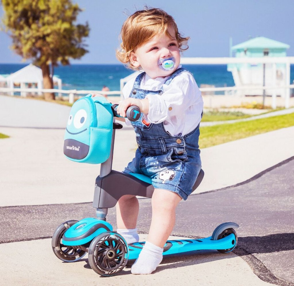 toddler sitting on seat of a blue scooter