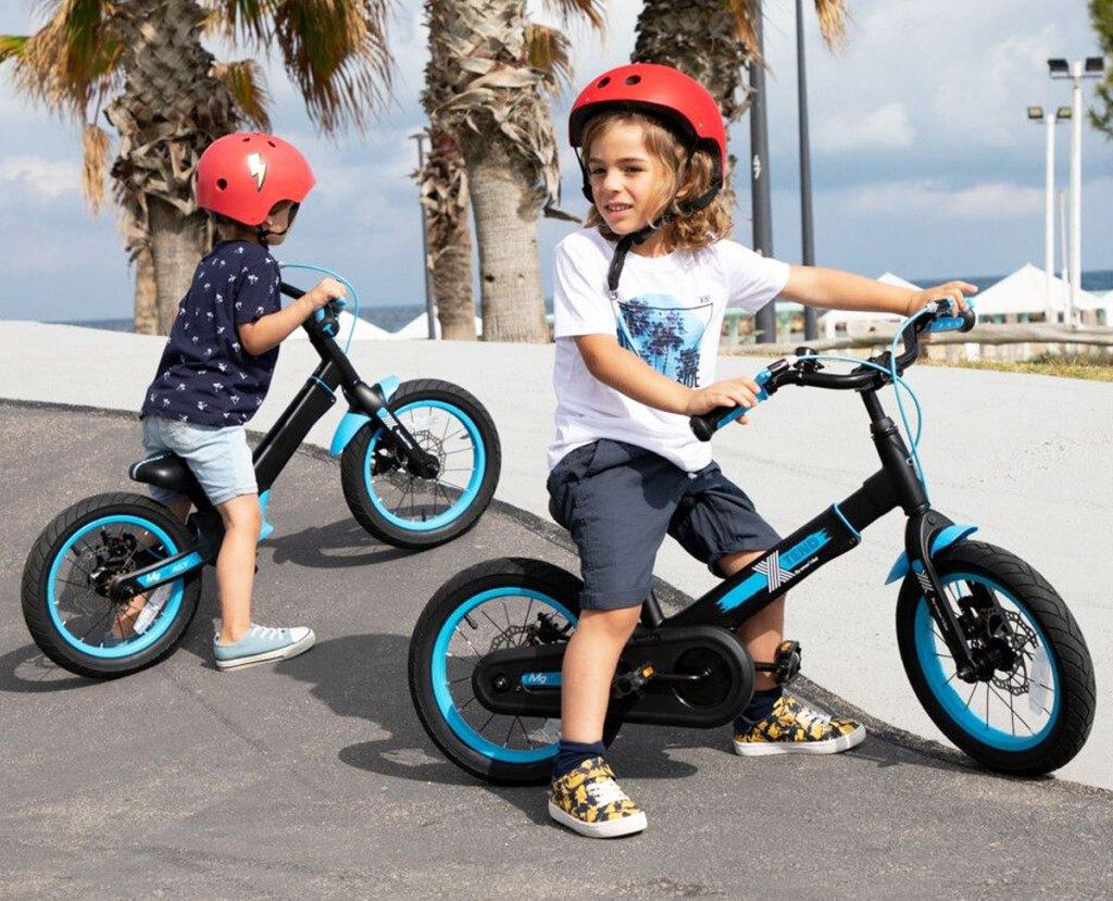 two boys on blue and black balance bikes