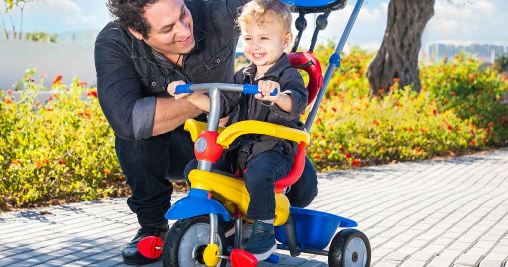 man kneeling next to toddler on a colorful tricycle stroller