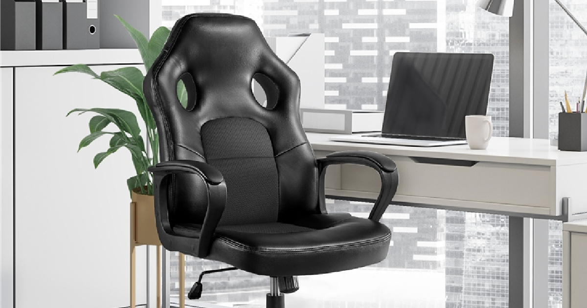black padded high back computer chair in front of plant and next to desk