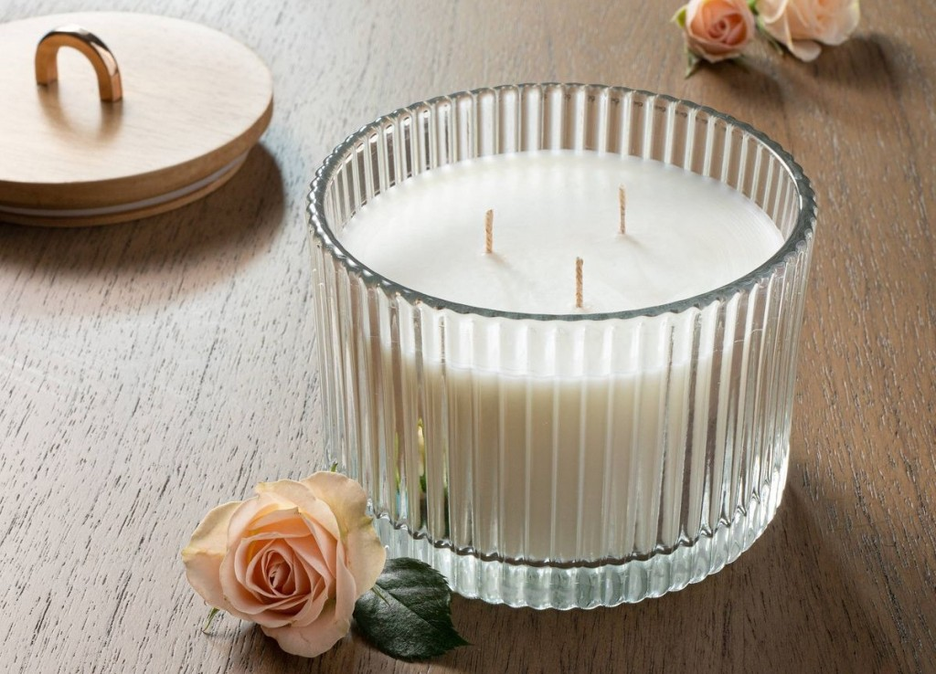 candle with roses by it
