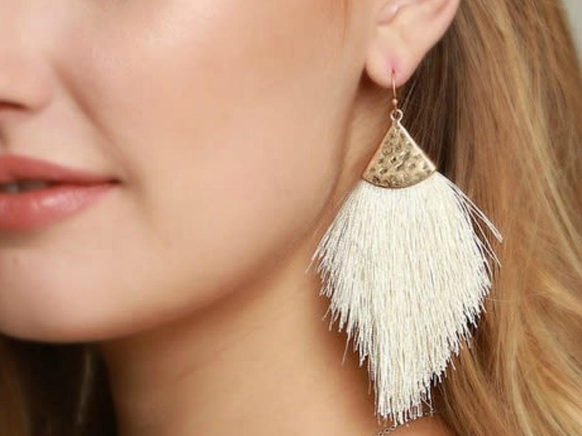 Woman wearing a white tassel style earring