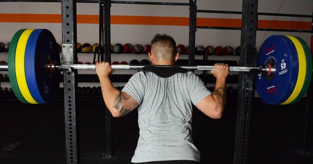 man with a barbell and weights on his shoulders