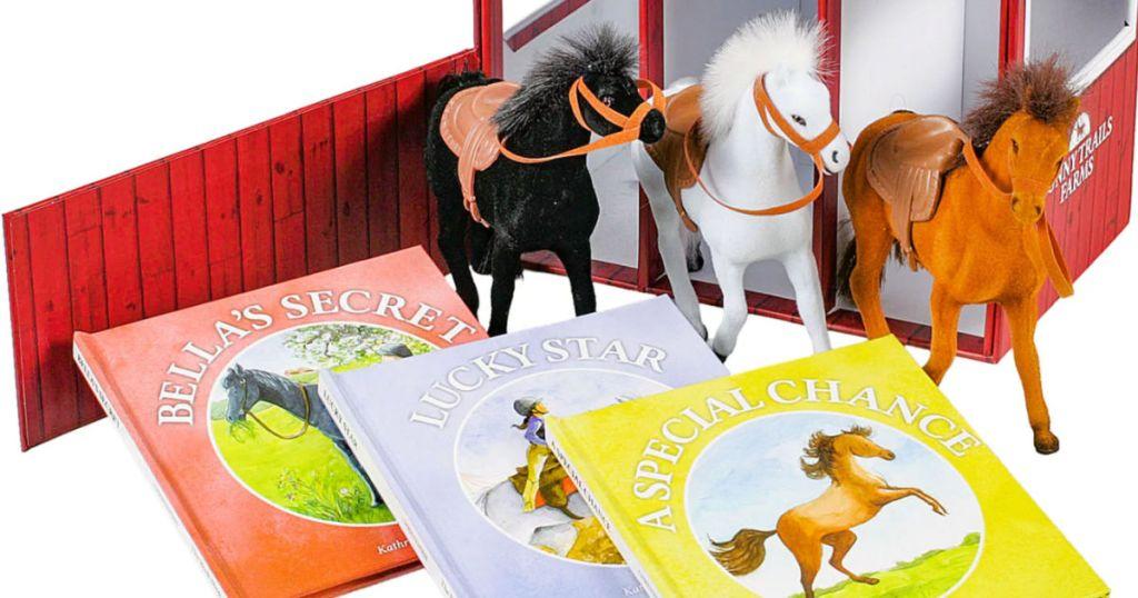 three toy horses next to books