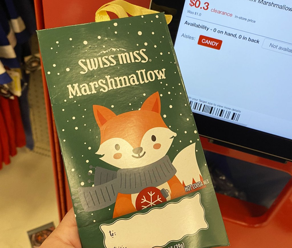person holding up a green swiss miss hot cocoa packet ornament at a target price scanner