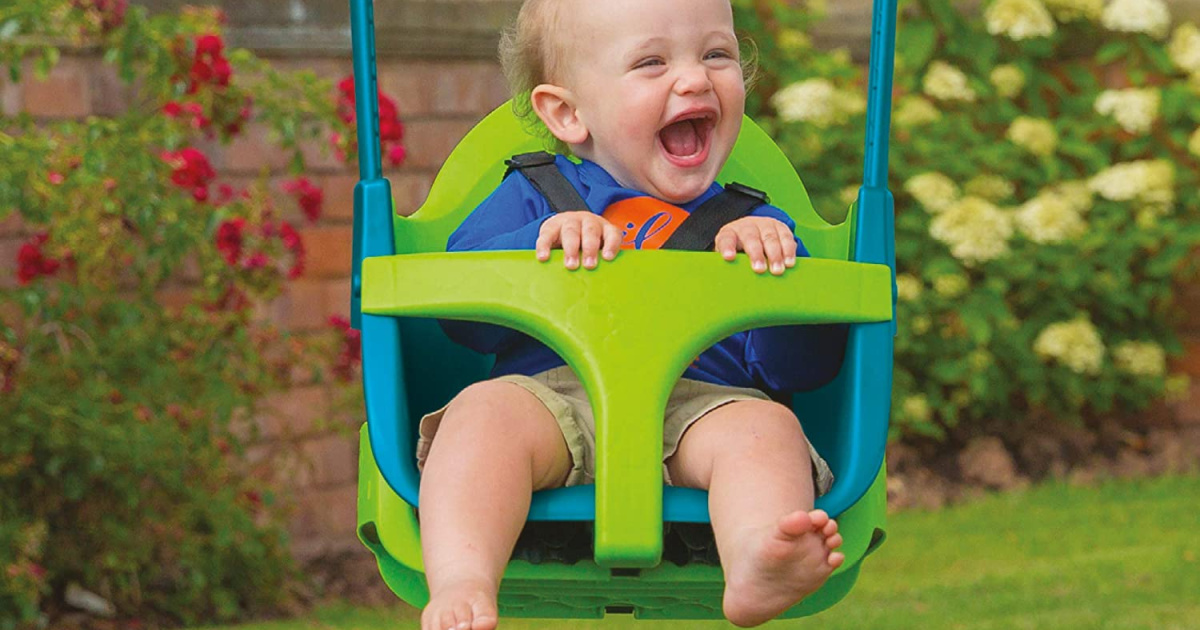 laughing baby in a blue and green kids swing