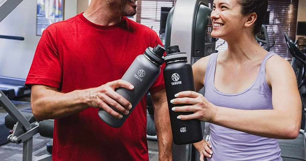 man and woman holding Takeya 40oz Water Bottle in a gym