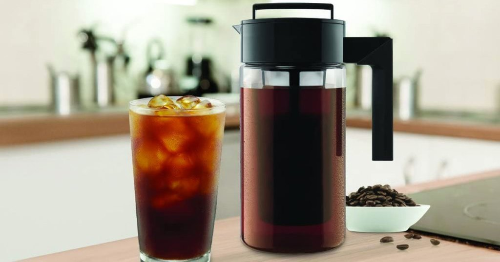 cold brew coffee pitcher on kitchen counter next to glass filled with coffee