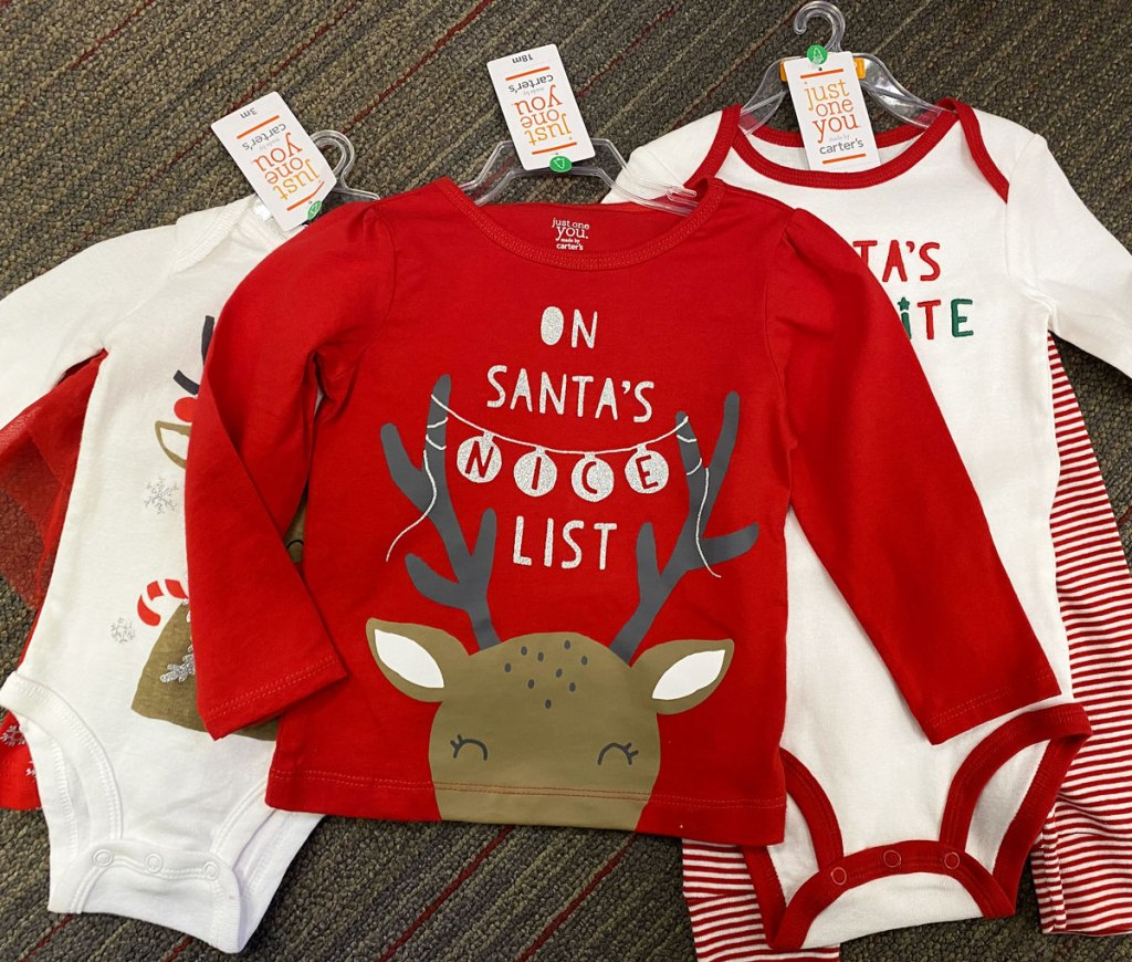 three pieces of carter's holiday baby apparel laid out on store floor