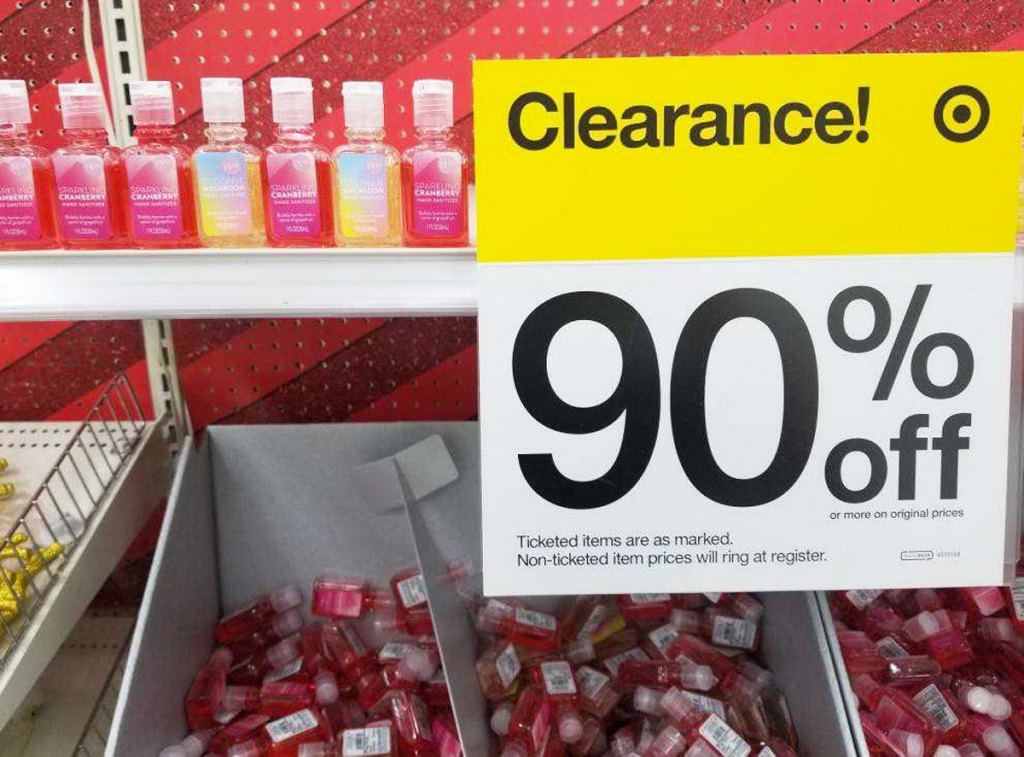 small holiday hand sanitizers on a target shelf with a yellow and white 90% off clearance sign