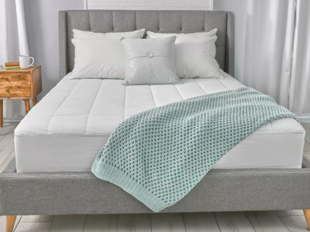 mattres pad on a grey bed frame with a light aqua on top of the bed