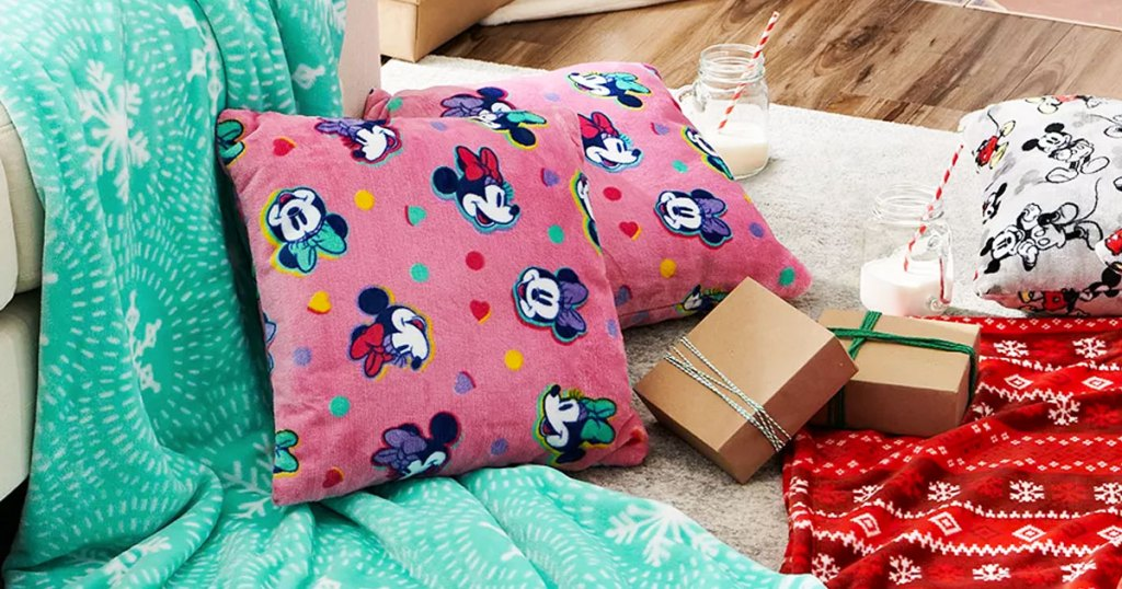 plush pink minnie mouse print throw pillows on floor near plush throw blankets and wrapped gift boxes