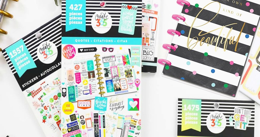 the happy planner sticker sheets and striped notebook on a table