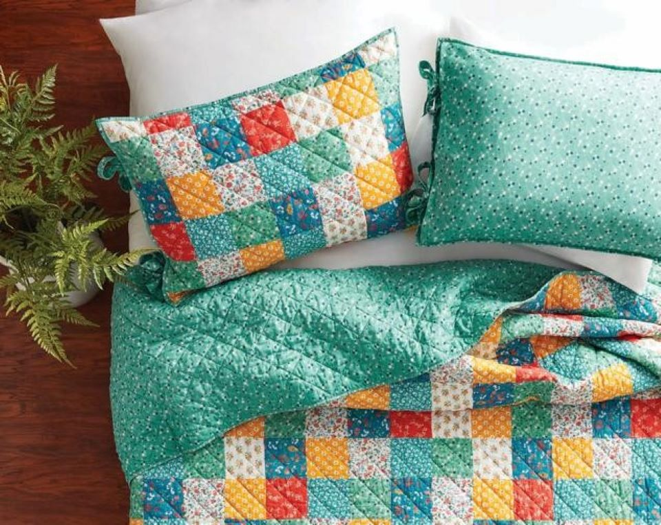 patchwork pillows and quilt on a bed