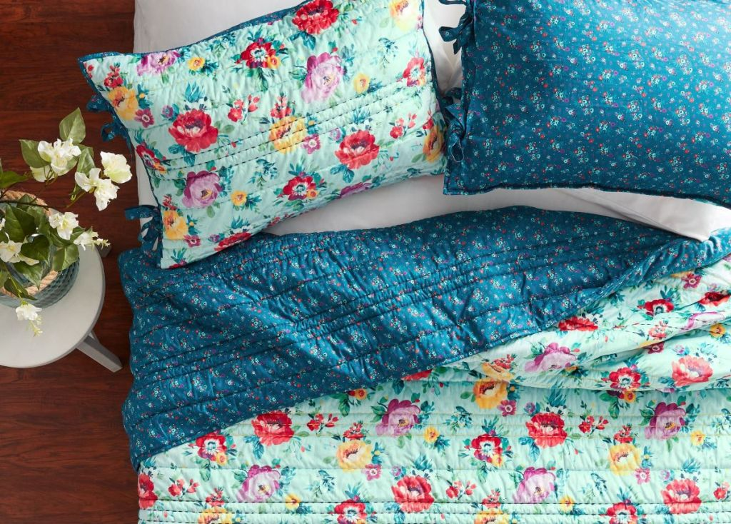bed with floral quilt and pillows