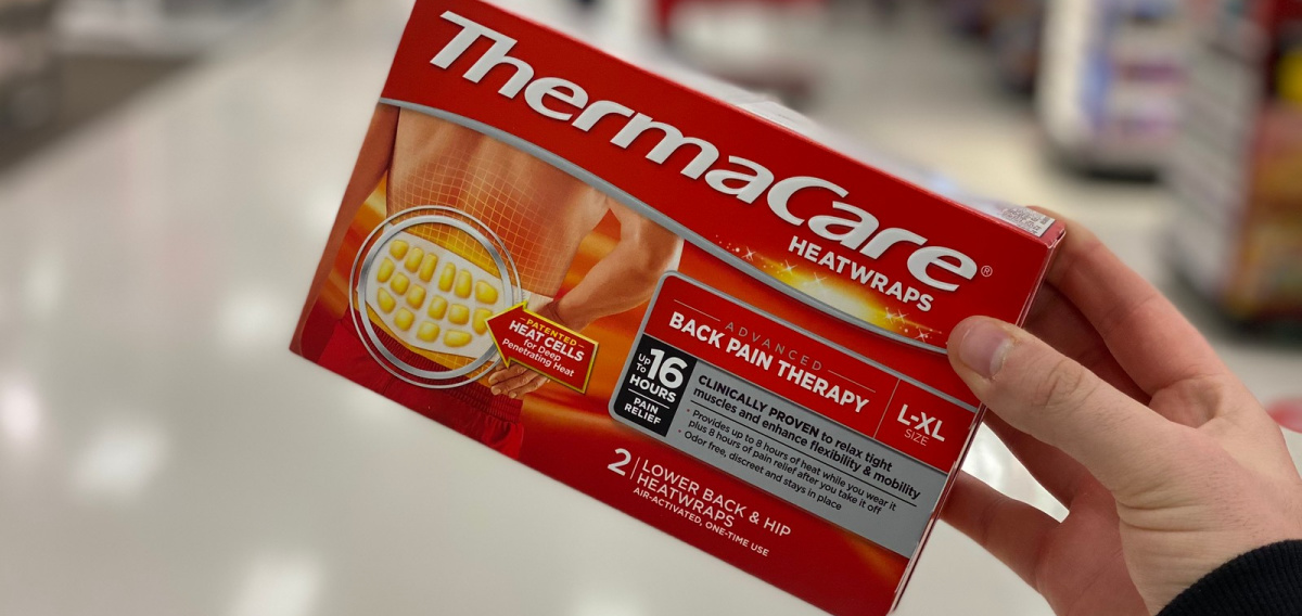 hand holding a box of Thermacare Wraps in a store