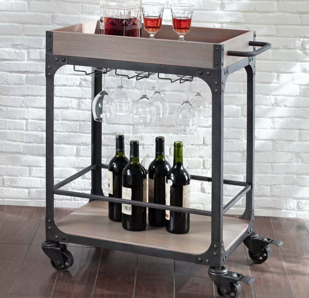 wood and metal bar cart with wine glasses and bottles of wine on it