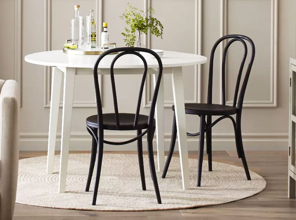 two black dining chairs at a white table