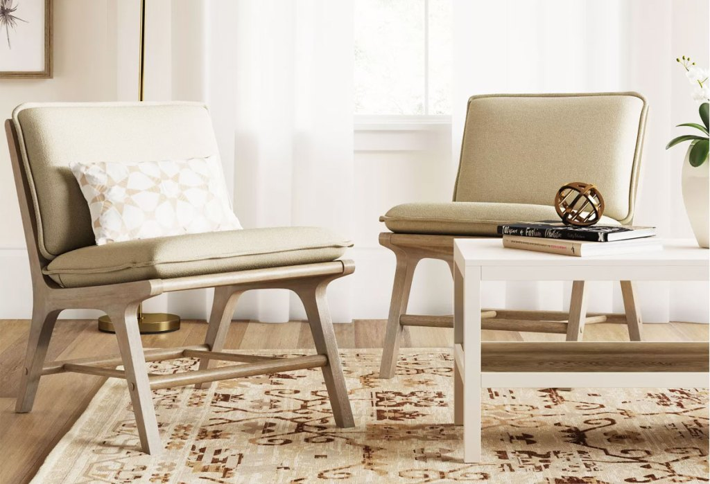 two wood accent chairs with taupe cushions on them