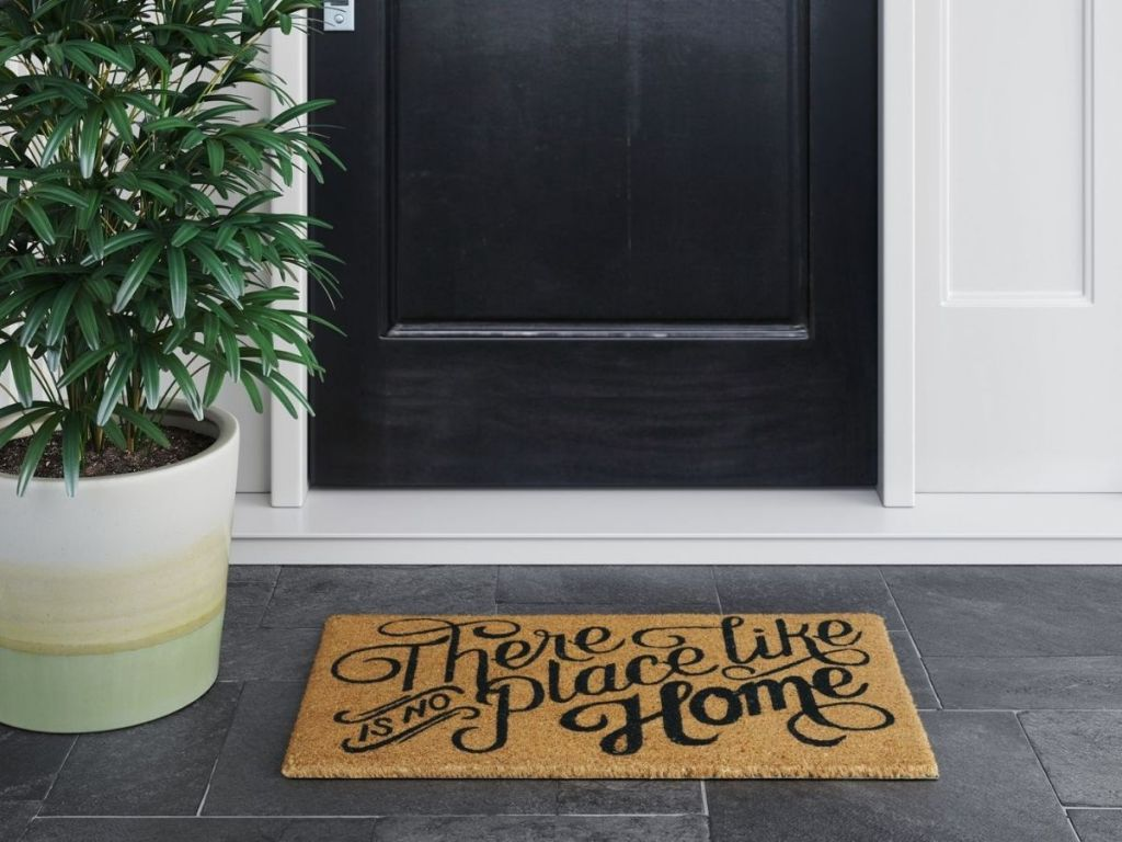 There's No Place Like Home Doormat in front of front door on porch next to a potted plant