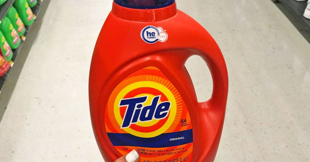 person with white finger nails holding up a bright orange bottle of tide liquid laundry detergent