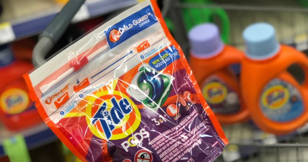 hand holding pack of tide pods with liquid in the background