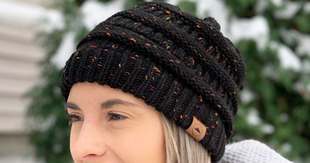 woman with blonde hair wearing a black cable knit beanie with multi-color specks in the yarn