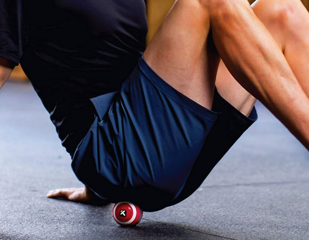 man in navy blue gym shorts rolling on a small red foam massage ball on gym floor