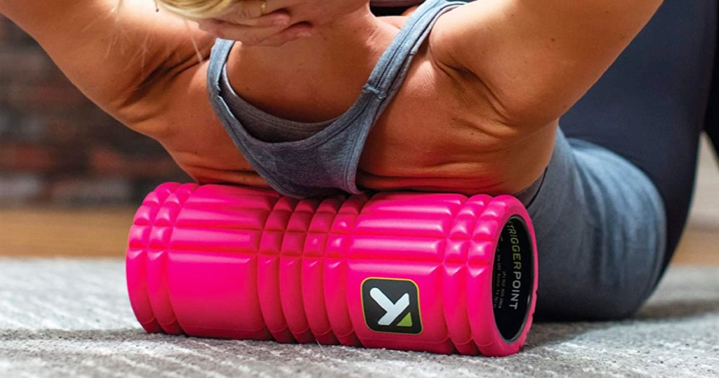 woman in a grey tank top rolling out her back on a hot pink foam roller
