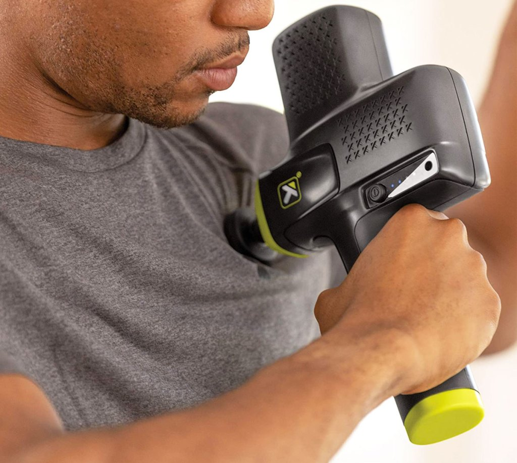 man in grey shirt holding a black and green handheld massage gun to his chest