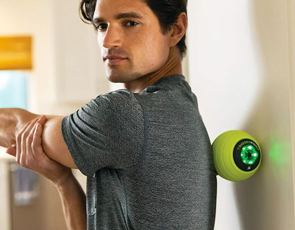 man in grey shirt leaning against a green massage ball against a white wall