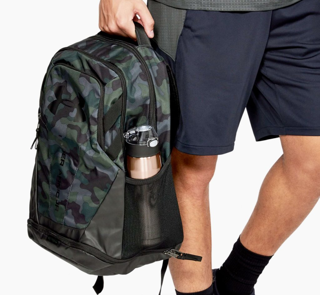 man holding a camo print under armour backpack