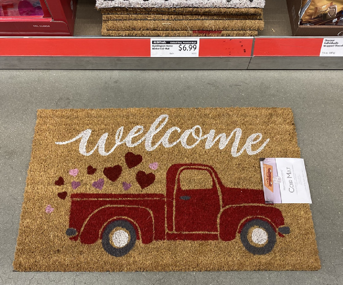 coir welcome rug showing a red truck and hearts laying on an aldi store floor