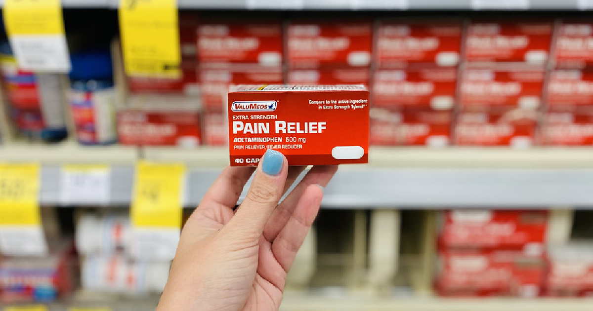 hand holding a box of pain reliever in front of a store display